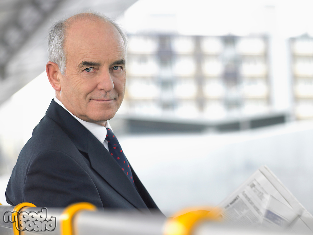 Smiling mature Businessman Sitting on Bench with newspaper looking over shoulder