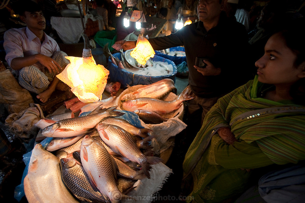 A woman looks on as a man buys fish from a vendor at the Santinagar market in Dhaka, Bangladesh.