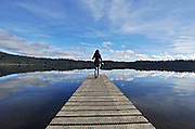 Woman stand at the end of a quay overlooking a lake