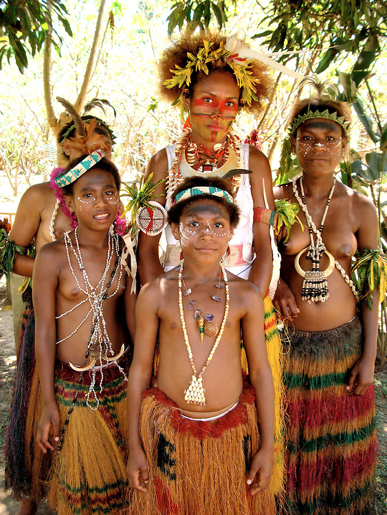 Papuan Tribe Women After Performing Sing-sing in Port Moresby, Papua New Guinea<br /> North of Australia in the Pacific Ocean is the island of New Guinea. In the west is the capital city of Port Moresby.  Papua New Guinea&rsquo;s history includes headhunting, cannibalism, frequent earthquakes, active volcanoes and one WWII&rsquo;s largest military campaigns.  There are numerous tribes, ethnic groups and over 800 indigenous languages.  Most people live in small villages and rely on primitive hunting, fishing and farming.  Sea shells were the primary currency until around 1930.  These girls had just performed a ritual dance called &ldquo;sing sing.&rdquo;  Their paint and feathers represent local birds and animals.