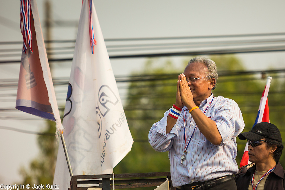 "09 DECEMBER 2013 - BANGKOK, THAILAND: SUTHEP THAUGSUBAN, former Deputy Prime Minister of Thailand and leader of anti-government protests, acknowledges the crowd as he arrives at Government House in Bangkok. Thai Prime Minister Yingluck Shinawatra announced she would dissolve the lower house of the Parliament and call new elections in the face of ongoing anti-government protests in Bangkok. Hundreds of thousands of people flocked to Government House, the office of the Prime Minister, Monday to celebrate the collapse of the government after Yingluck made her announcement. Former Deputy Prime Minister Suthep Thaugsuban, the organizer of the protests, said the protests would continue until the ""Thaksin influence is uprooted from Thailand."" There were no reports of violence in the protests Monday. The collapse of the government leaves Thailand with an unprecedented power vacuum.      PHOTO BY JACK KURTZ"