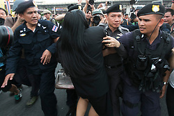 © Licensed to London News Pictures. 26/05/2014. A PDRC supporter is escorted out by police for her own safety after taunting anti-coup protestors during a Anti-Coup protest in Bangkok Thailand. Today Thailand's King formally approved Thai army chief General Prayut Chan-O-Cha as head of the nation's new military junta.  Photo credit : Asanka Brendon Ratnayake/LNP