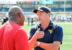 Sep 16, 2017; Morgantown, WV, USA; West Virginia Mountaineers head coach Dana Holgorsen talks with Delaware State Hornets head coach Kenny Carter before the game at Milan Puskar Stadium. Mandatory Credit: Ben Queen-USA TODAY Sports