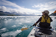 Woman kayaking on Aialik Bay, Kenai Fjords National Park, Alaska