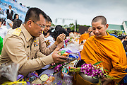 "22 JULY 2014 - BANGKOK, THAILAND: Thai officials make merit by presenting alms to Buddhis monks during a merit making ceremony at Sanam Luang. Hundreds of Thai military officers and civil servants attended a Buddhist chanting service and merit making ceremony to mark the 2nd month anniversary of the May 22 coup that deposed the elected civilian government and ended nearly six months of sometimes violent anti-government protests. The ruling junta said the ceremonies Tuesday were the kickoff to a ""Festival to Bring Back Happiness of the People of the Nation."" There will be free concerts, historical pageants and movies at Sanam Luang, a large parade ground near the Ministry of Defense in Bangkok.    PHOTO BY JACK KURTZ"