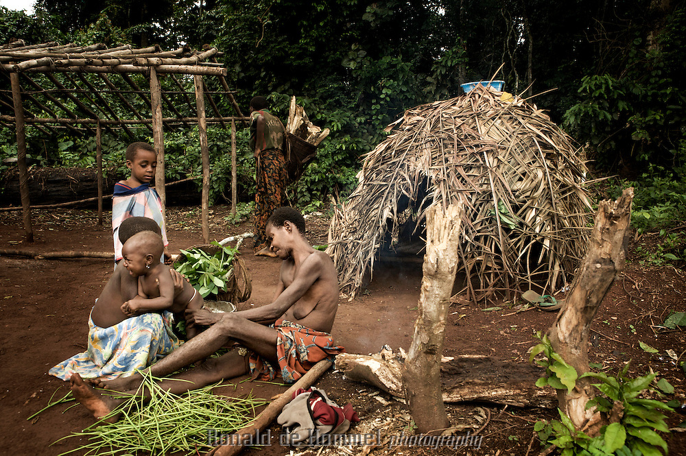 A small BaAka family in front of a hut. The BaAka Pygmies are a small minority int the forest lowlands on the border of CAR and DRC. they have traditionally been treated like slaves in this area. The nomadic tribes live in temporary camps in the jungle or near villages.