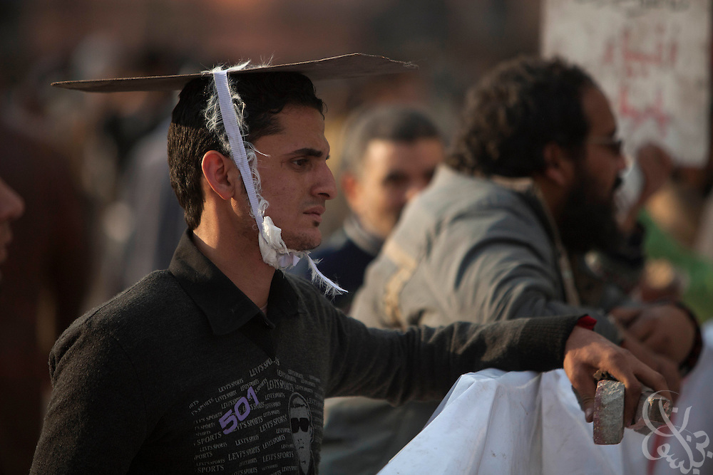 An anti-Mubarak protester wears a makeshift helmet and holds a handful of stones during clashes with pro-Mubarak protesters on the edge of Tahrir Square February 02, 2011in Cairo Egypt. Both sides faced off today, battling for control of the square which has been at the center of more than a week of ongoing protests across Egypt..(Photo by Scott Nelson)