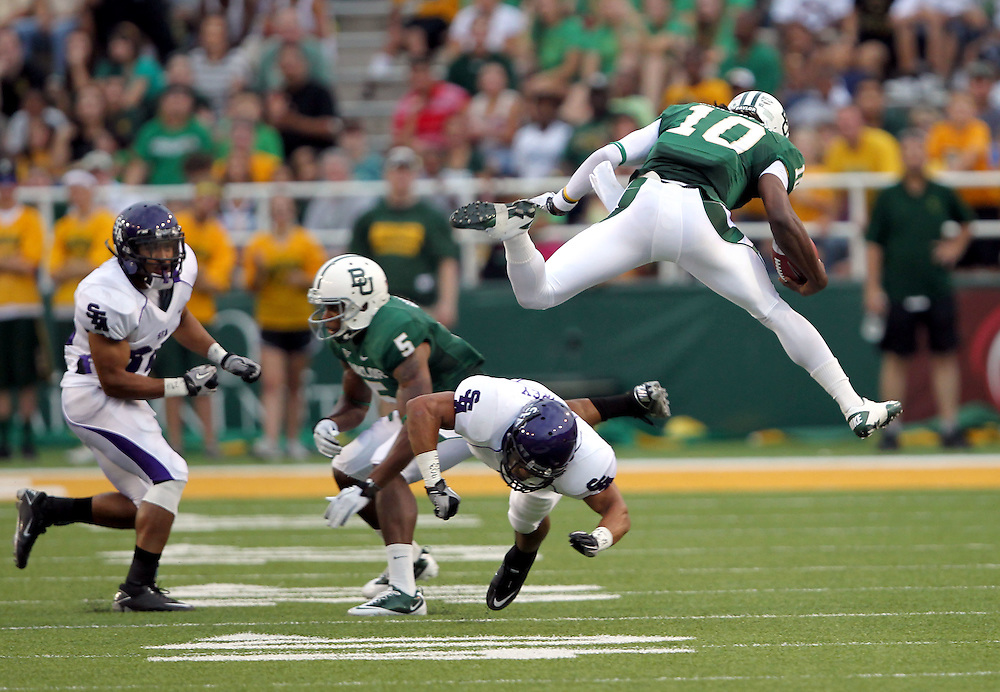 Baylor quarterback Robert Griffin III (10) hurdles over Stephen F. Austin defensive back Josh Aubrey (37) for a first down during an NCAA college football game, Saturday, Sept. 17, 2011, in Waco, Texas. Baylor won 48-0.