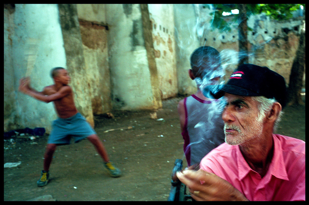On the corner of Damas and Acosta Streets in Old Havana, Zaúl Sierra Palmero, 61, smokes a cigar as kids engage in a sandlot baseball game. It was el Día de los Pioneros in Cuba and the children had the day off from school.