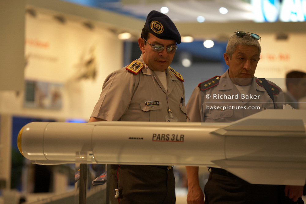 Two army officers from Ecuador admire an air-to-ground PARS 3 LR missile at the Paris Air Show, Le Bourget France. The two men (the man on the right's name badge says M Pazmino), admire the sleek design of the missile called PARS 3 LR in German but known as TRIGAT-LR (Third Generation AntiTank, Long Range) and AC 3G in the French military, the missile is a high-precision 'fire-and-forget' weapon system for engaging mobile and stationary targets equipped with the latest generation of armour protection, such as tanks, field fortresses, bunkers and other high-value targets. The system can launch up to four salvos in eight seconds. .The Paris Air Show is a commercial air show, organised by the French aerospace industry whose purpose is to demonstrate military and civilian aircraft to potential customers.