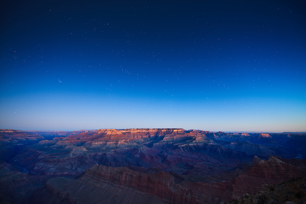 A long-exposure captures faint light of pre-dawn striking Wotans Thron with a star filled sky above. Grand Canyon National Park in Arizona.