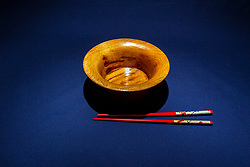 Hand turned wooden oak bowl on dark blue background with decorated red colored chopsticks