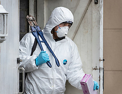 © Licensed to London News Pictures. 05/01/2019. Farnham, UK. A police forensics officer emerges from a rubbish bin cupboard next to a property in Farnham, Surrey after a couple were arrested in connection with the murder of a man on a train yesterday. A murder investigation has been launched after the man was attacked while on board the 12. 58pm train service travelling between Guildford and London Waterloo. A man and a woman have been detained by police in Farnham in connection with the murder. Photo credit: Peter Macdiarmid/LNP