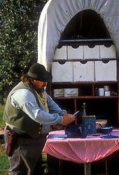 man preparing food on the back of a western covered wagon