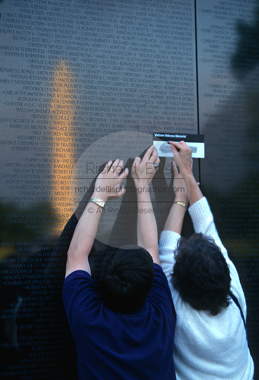 Family members trace a name from the Vietnam Veterans Memorial wall November 11, 1996 in Washington, DC.