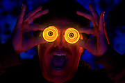 A happy man holding glowing spiral binoculars.Black light
