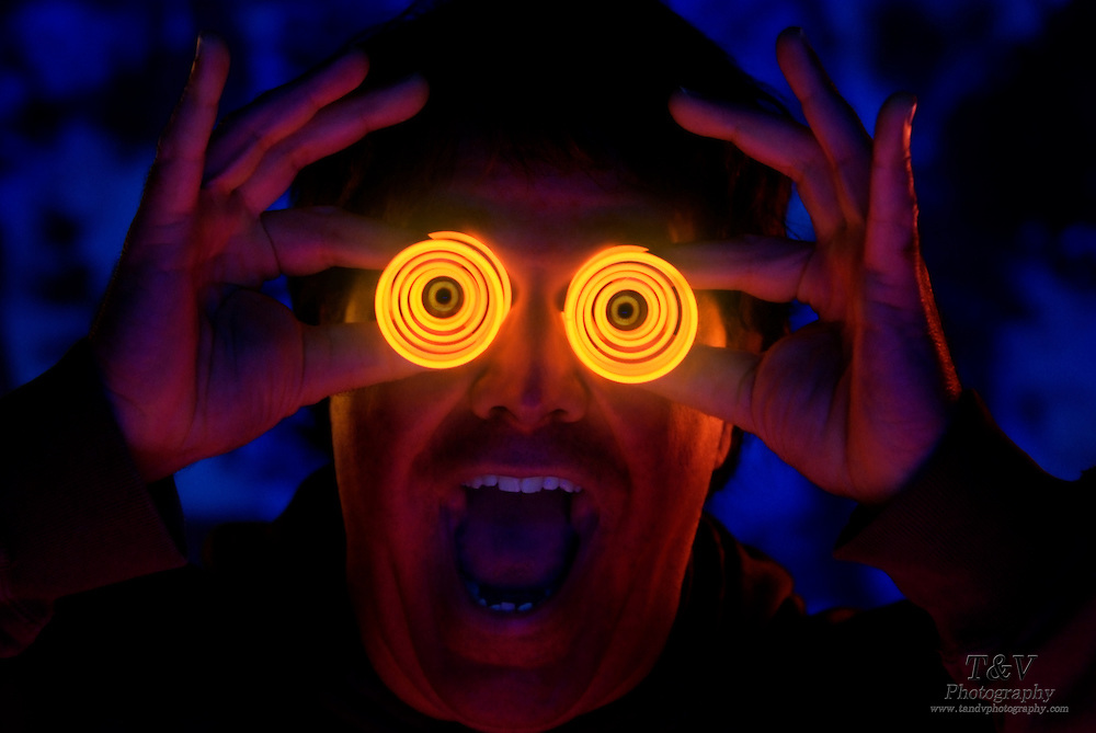 A happy man holding glowing spiral binoculars.Black light