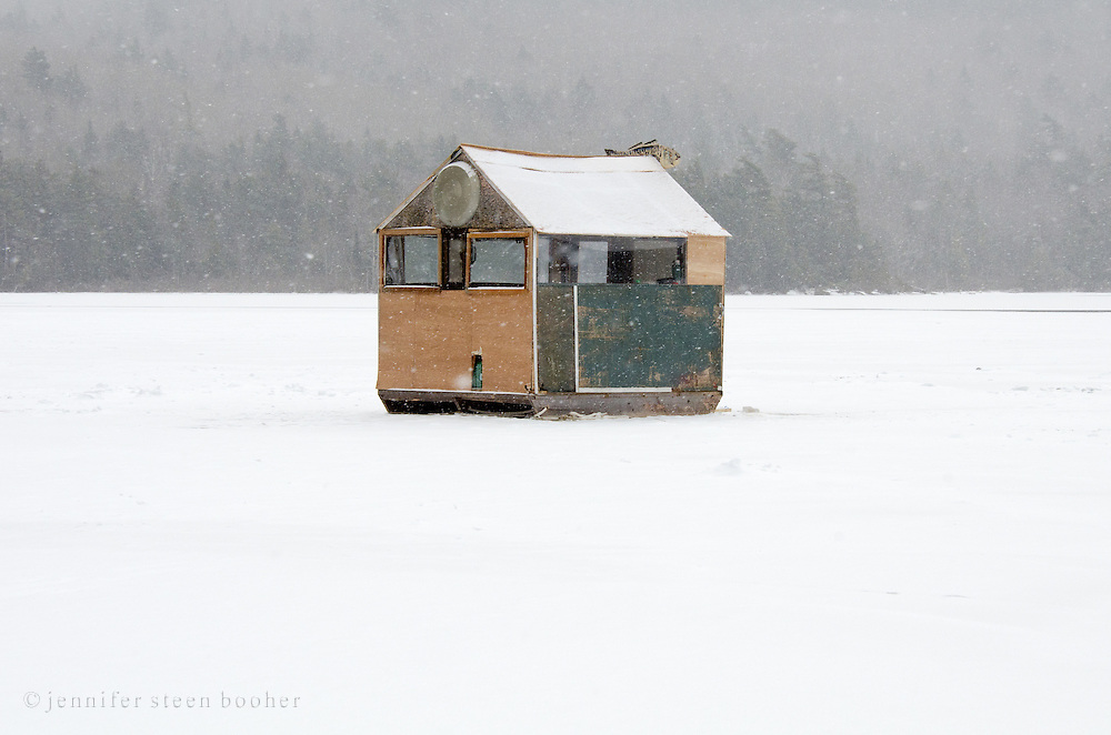 A large green ice fishing shack in a snowstorm.