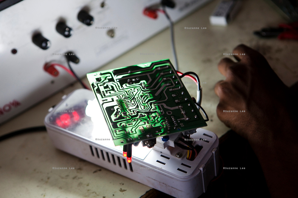An Indian student inspects and tests a solar light circuit board in class in the Barefoot College in Tilonia village, Ajmer, Rajasthan, India. Photo by Suzanne Lee for Panos London