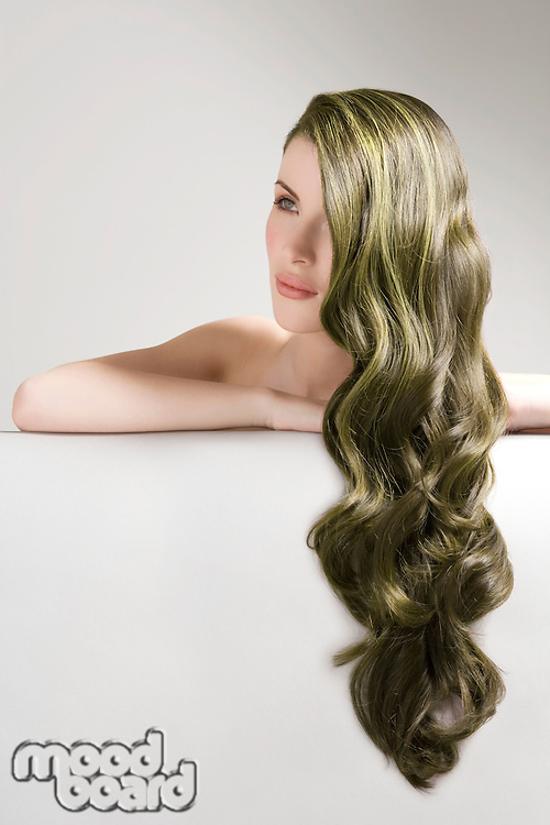 Thoughtful woman with long green dyed hair against gray background