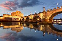 Blick über den Tiber zur Engelsbrücke und Engelsburg in Rom bei Nacht.