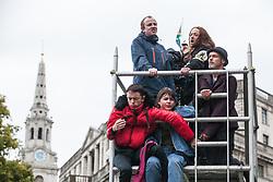 London, UK. 7 October, 2019. Climate activists from Extinction Rebellion are glued to a scaffold tower to block a road around Trafalgar Square on the first day of International Rebellion protests to demand a government declaration of a climate and ecological emergency, a commitment to halting biodiversity loss and net zero carbon emissions by 2025 and for the government to create and be led by the decisions of a Citizens' Assembly on climate and ecological justice.