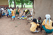 Hassana Ibrahim, 11, (right) is eating a nutritional meal available under the School Feeding Program run by the local NGO SEND, while sitting in the courtyard of the small rural institution she is attending in Boggu, Tamale, northern Ghana. Other pupils are in a line in order to receive the same lunch.
