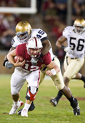 November 28, 2009; Stanford, CA, USA;  Stanford Cardinal quarterback Andrew Luck (12) is tackled by Notre Dame Fighting Irish linebacker Darius Fleming (45) during the second quarter at Stanford Stadium. Stanford defeated Notre Dame 45-38.