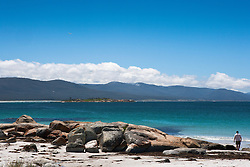 A single man walks along the beach at Bicheno on the east coast of Tasmania.