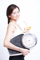Side view of young Asian woman holding banana and weight scale against white background