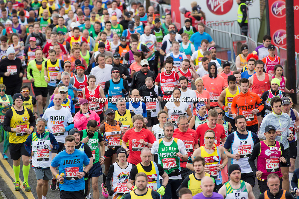 Runners crfossing the red start line at the beginning of The Virgin Money London Marathon, Sunday 24th April 2016.<br />