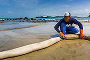 02 AUGUST 2013 - KOH SAMET, RAYONG, THAILAND:  A worker lays out containment booms on Ao Prao beach on Koh Samet as cleanup after an oil spill over the weekend continues. About 50,000 liters of crude oil poured out of a pipeline in the Gulf of Thailand over the weekend authorities said. The oil made landfall on the white sand beaches of Ao Prao, on Koh Samet, a popular tourist destination in Rayong province about 2.5 hours southeast of Bangkok. Workers from PTT Global, owner of the pipeline, up to 500 Thai military personnel and volunteers are cleaning up the beaches. Tourists staying near the spill, which fouled Ao Prao beach, were evacuated to hotels on the east side of the island, which was not impacted by the spill. Officials have not said when Ao Prao beach would reopen. PTT Global Chemical Pcl is part of state-controlled PTT Pcl, Thailand's biggest energy firm.   PHOTO BY JACK KURTZ
