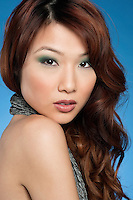 Portrait of a beautiful young Asian woman over colored background