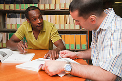 Man with hearing impairment with fellow student in university library.
