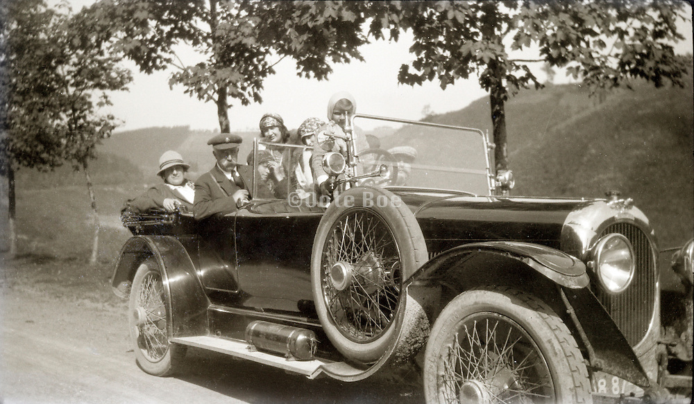 family posing in their car on a rural countryside road 1920s