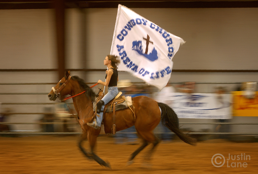 A young woman on a horse carries the flag of the Cowboy Church in Amarillo, TX that holds a Christian rodeo each Thursday in their own arena behind the church, Thursday July 14, 2005. The church rodeo, in which semi-professional bull riders compete, is designed to bring in people who are interested in the sport then expose them to the teachings of Jesus.