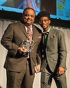 Roland Martin receives a distinguished alumni award from Yates High School student Reginald Pierre-Antonie during the State of the Schools luncheon at the Hilton of the Americas, February 15, 2017.