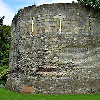 Multangular Roman Tower in York, England<br /> York was founded as Roman fortress city named Eboracum in 71 AD. This military post was used by several emperors to launch campaigns across Britannia (present day Great Britain). As its strategic value grew, so did its strength. At first it was constructed with wood. By 300 AD, it was a large stone citadel. The Multangular Tower is one of the few remaining remnants. The 19 foot tall, ten-sided defense contained a catapult.  On the right is part of a 76 foot Roman wall. These historic landmarks are located in the Museum Gardens.