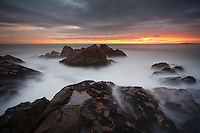 A spectacular sunset as the sun illuminates a dramatic sky as photographed from a rocky outcrop on  the coast line of West Coast National Park in South Africa.