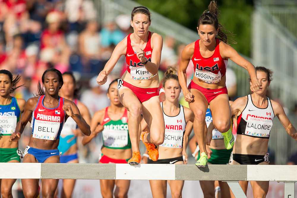 Shalaya Kipp (L) and teammate Ashley Higginson of the United States lead the pack over the water barrier during the women's steeplechase at the 2015 Pan American Games at CIBC Athletics Stadium in Toronto, Canada, July 24,  2015.  AFP PHOTO/GEOFF ROBINS