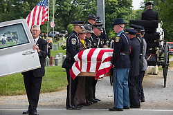 Police officers from around the state carry fallen Bardstown police officer Jason Ellis' body from the hearse and place it on a carriage that carried him to his burial plot, Thursday, May 30, 2013 at High View Cemetery in Chaplin. Photo by Jonathan Palmer
