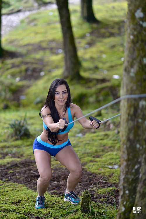 Hispanic woman in her forties exercising fitness workout with resistance bands in a forest.   May 29, 2014. (Kike Calvo via AP Images)