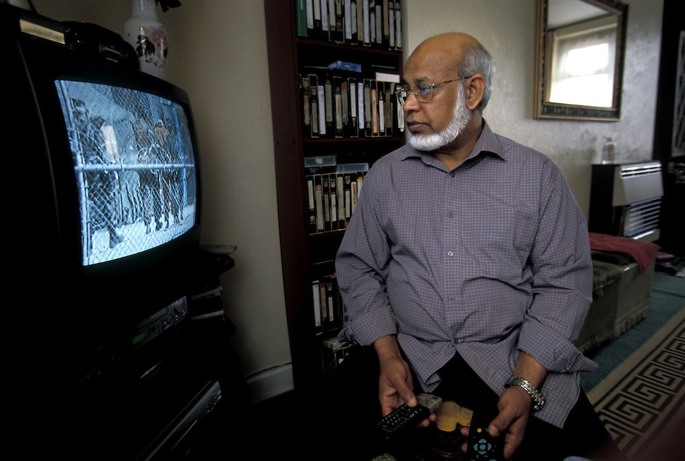 Riasoth Ali Ahmed, 63 from Tipton, father of Rhuhel Ahmed, 21  who was captured in Afghanistan in 2001 and accused of fighting for the Taliban. Rhuhel is now being detained by the US at the Guantanamo Bay military base at the edge of Cuba. Photographed watching a video of his son at the family home in Tipton in the East Midlands, UK.