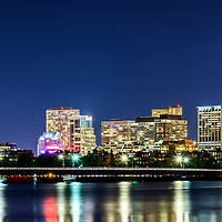 Boston skyline at night panorama photo with Back Bay buildings, Harvard Bridge, Charles River, John Hancock Tower, and Prudential Tower. Boston Massachusetts is a major city in the Eastern United States of America. Panorama photo ratio is 1:3.