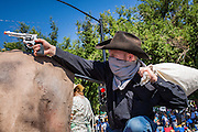 30 JUNE 2012 - PRESCOTT, AZ:  An old west reenactor participates in a fake gunfight at the Prescott Frontier Days Rodeo Parade. The parade is marking its 125th year. It is one of the largest 4th of July Parades in Arizona. Prescott, about 100 miles north of Phoenix, was the first territorial capital of Arizona.    PHOTO BY JACK KURTZ