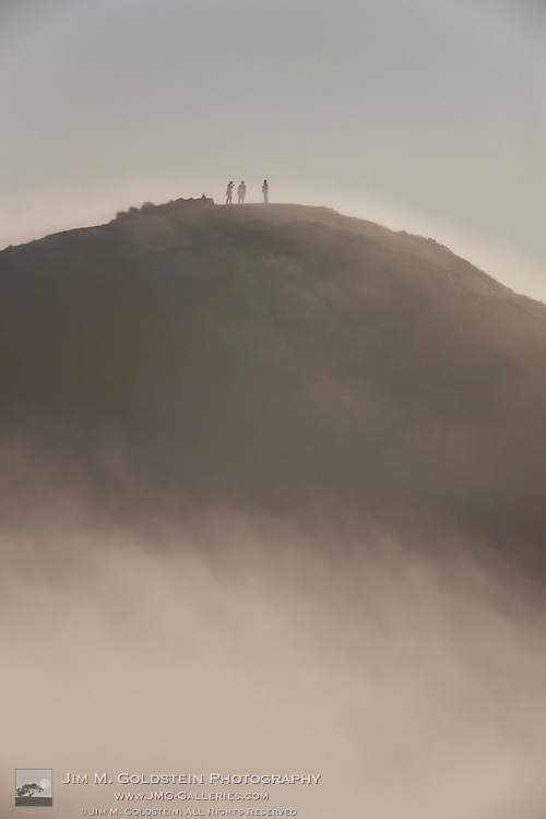 Hikers atop a fog shrouded Twin Peaks mountain top - San Francisco, California