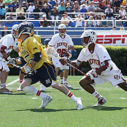 Drexel Attacker Jules Raucci (5), LEFT, position himself towards the goal as Denver Midfielder Terry Ellis (12), RIGHT, defends in the second half of The NCAA Division I Men's Lacrosse Tournament game between the No. 5 seed Denver and No. 12 ranked Drexel Sunday, May. 18, 2014 at Delaware Stadium in Newark, DEL