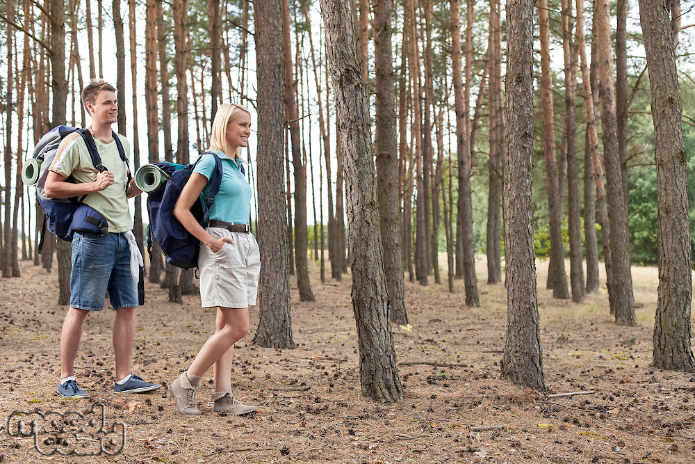Full length of happy young couple hiking in forest