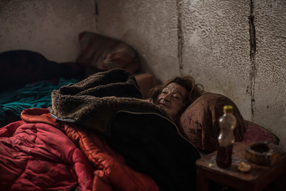 DEBALTSEVE, UKRAINE - FEBRUARY 7, 2015: Lyuba Sklyarova lies in her bed after recent shelling caused her to spill hot soup onto herself, leaving her effectively paralyzed, in Debaltseve, Ukraine. Her husband was injured in the same shelling but ventured out to collect drinking water. The Ukrainian-controlled town, surrounded on three sides by rebel forces, has been undergoing heavy shelling for more than a week, but a brief ceasefire allowed many residents to evacuate and others to simply venture out from their homes. CREDIT: Brendan Hoffman for The New York Times