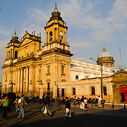 Locals walk in front of the Catedral Metropolitana facing Parque Central (officially the Plaza de la Constitucion) in the center of Guatemala City, Guatemala.